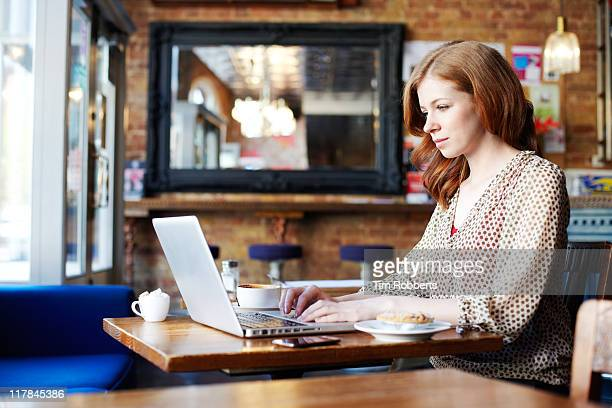 Woman working on laptop in coffee shop