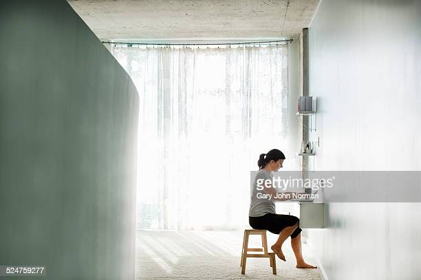 Woman working on laptop in empty appartment.