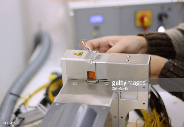 Woman working on machine for cutting and crimping wires