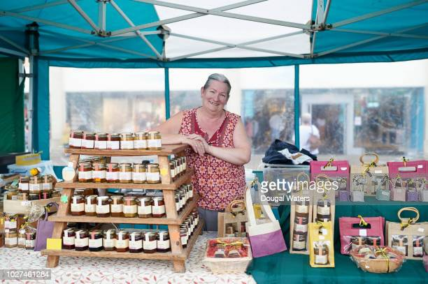 woman working on market stall selling homemade jam and preserves. - mercato luogo per il commercio foto e immagini stock