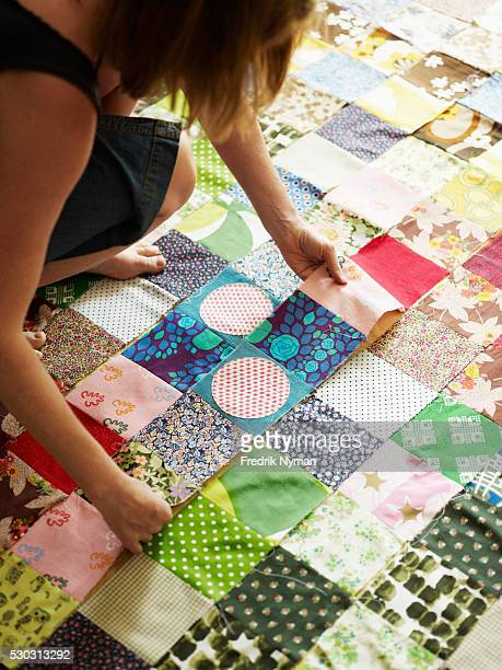 woman working on patches to make quilt - キルト ストックフォトと画像