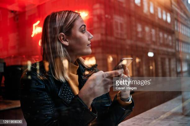 woman working on phone and looking away through the window at coffee shop. window reflexions. shot of a young blonde woman. - businesswoman stock pictures, royalty-free photos & images