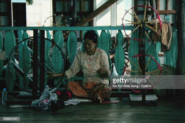 woman working on spinning wheel at home - ko ko htike aung stock pictures, royalty-free photos & images
