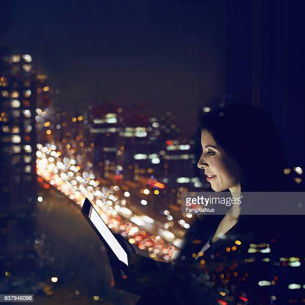 Woman working on tablet computer at night in office