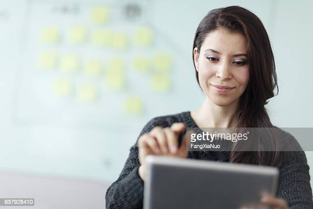 woman working on tablet computer in studio office - content stock pictures, royalty-free photos & images