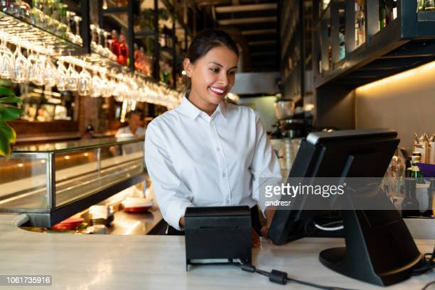 woman working on the cashier at a restaurant - party host stock pictures, royalty-free photos & images