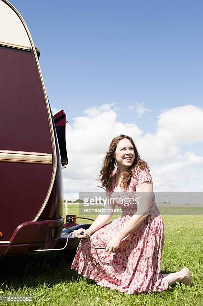 Woman working on trailer in field