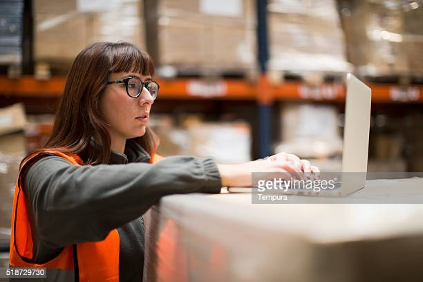 Woman working on warehouse using a laptop.