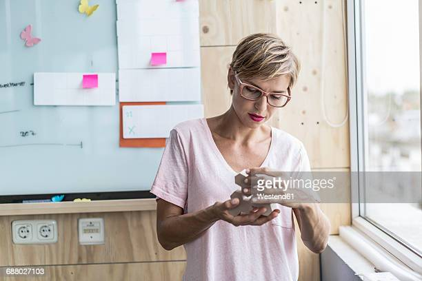 Woman working on wooden building blocks in modern office