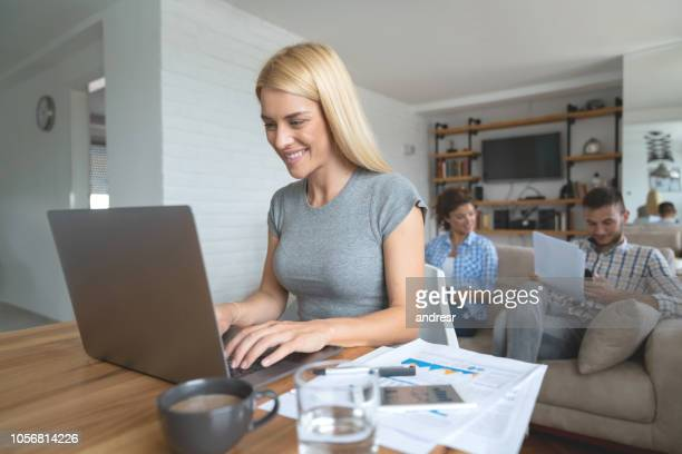 Woman working online at home with house mates in the background