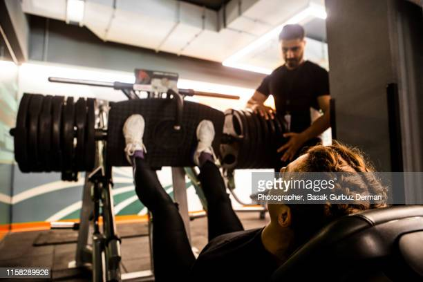 A woman working out on a leg press machine in a health club by the help of a male personal trainer