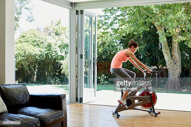 woman working out on exercise bike at home - peloton stock pictures, royalty-free photos & images