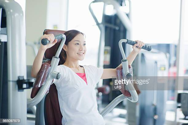 woman working out on exercise machine in a gym