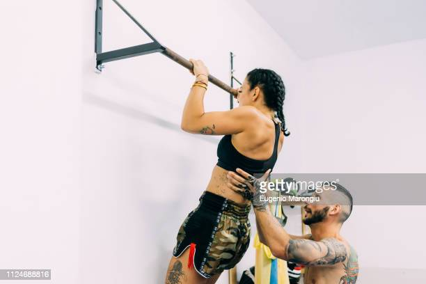 woman working out on metal bars - boxing shorts stock pictures, royalty-free photos & images