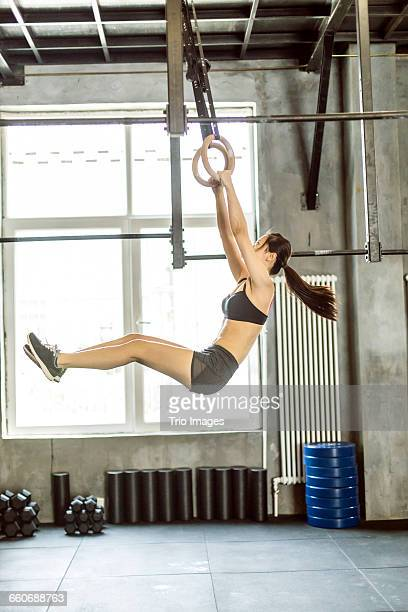 woman working out on rings in gym