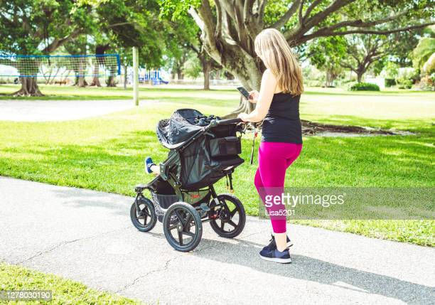 woman working out outdoors with cellphone and baby in stroller - carriage stock pictures, royalty-free photos & images