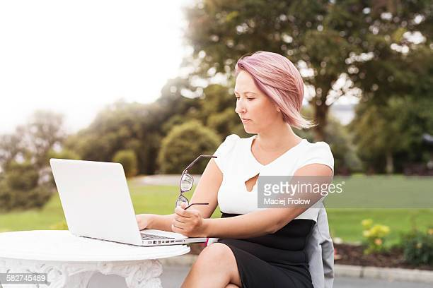 Woman working outdoors using laptop