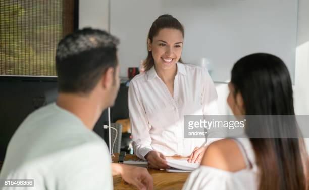 Woman working the front desk at a hotel and talking to a couple