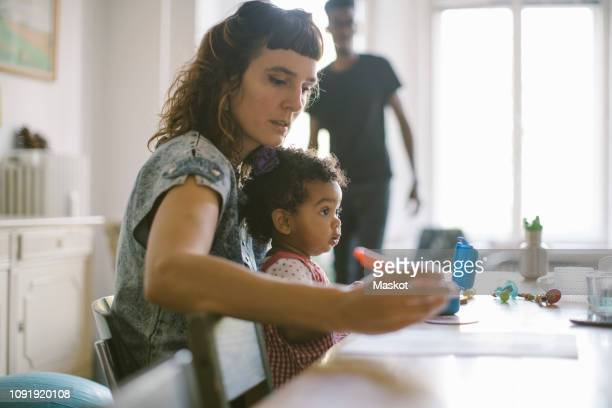 woman working while sitting with daughter at table in house - quarantäne stock-fotos und bilder