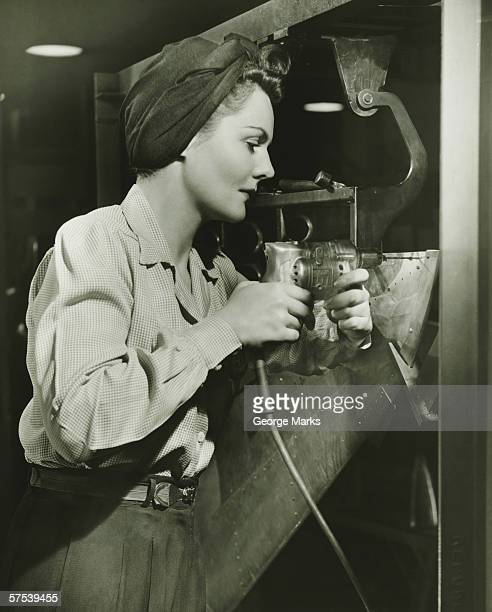 Woman working with electric drill in factory, (B&W)