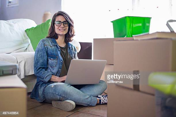 Woman working with her laptop at the new home