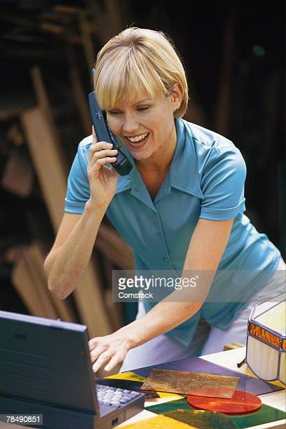 Woman working with laptop and telephone