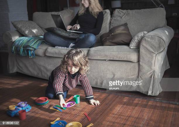 Woman working with laptop while child is playing with toys at home