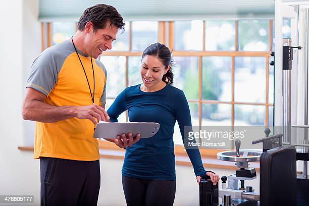 Woman working with personal trainer in gym