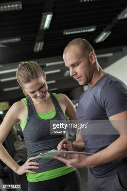 woman working with personal trainer in gym - checking sports stock pictures, royalty-free photos & images
