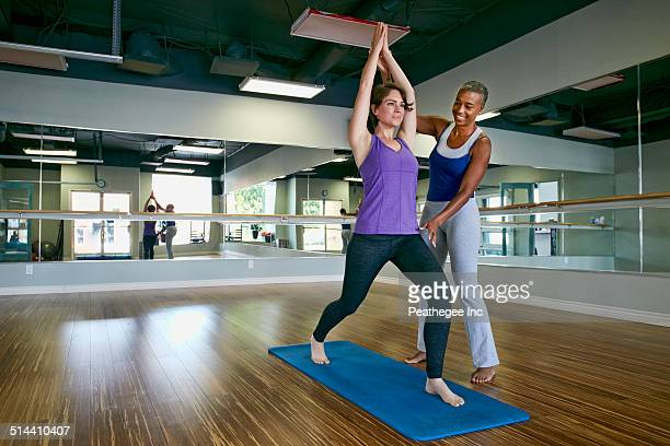 Woman working with yoga teacher in studio