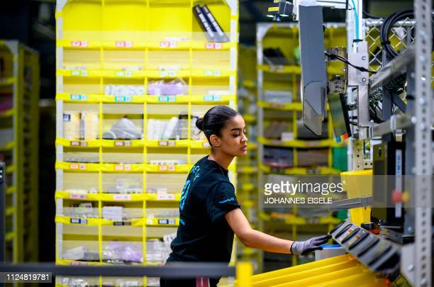 A woman works at a distrubiton station at the 855000squarefoot Amazon fulfillment center in Staten Island one of the five boroughs of New York City...