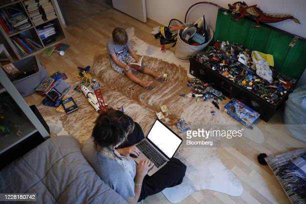Woman works at a laptop computer on the floor of a bedroom as a child sits alongside reading a book in this arranged photograph taken in Bern,...
