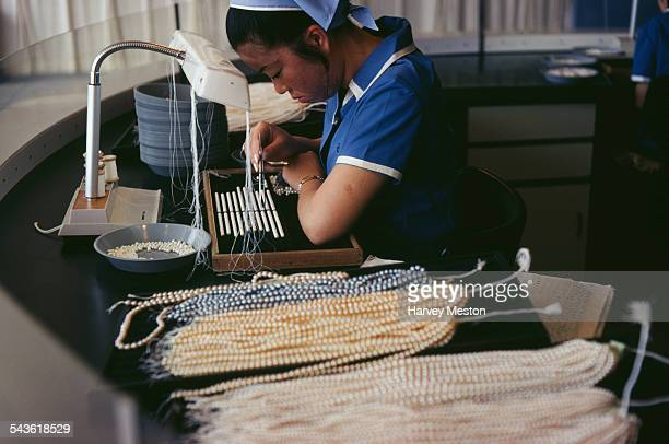 A woman works at a machine sorting pearls for necklaces in Japan June 1970