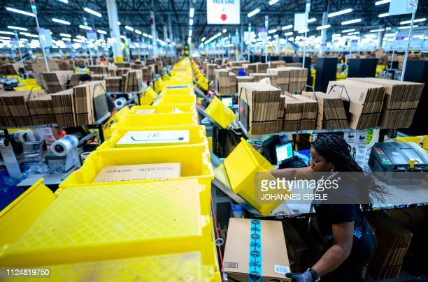 A woman works at a packing station at the 855000squarefoot Amazon fulfillment center in Staten Island one of the five boroughs of New York City on...