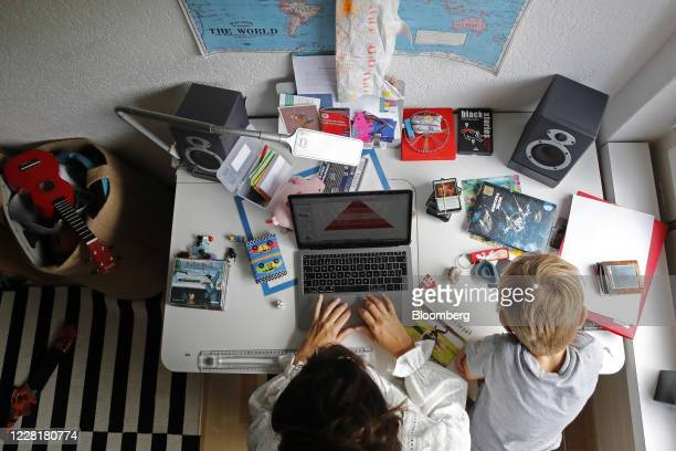 Woman works at an Apple Inc. Laptop computer on a desk in a bedroom as a child sits alongside in this arranged photograph taken in Bern, Switzerland,...