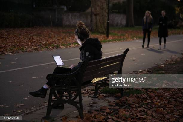 Woman works at dusk on a park bench on the first day of national lockdown on 5th of November 2020, East London, United Kingdom. The UK Govenrment...