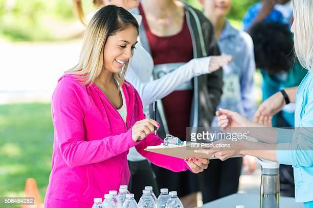 Mulher que trabalha na mesa de registo de caridade corrida
