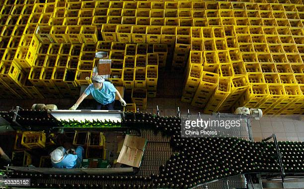A Woman works at the beer production line in Guangzhou Zhujiang Beer Group Company factory on August 6 2005 in Guangzhou of Guangdong Province South...