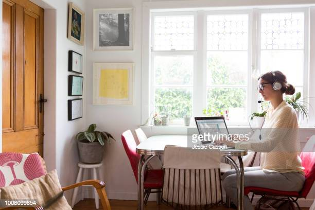 a woman works from her home at the table in her kitchen - working from home stock pictures, royalty-free photos & images