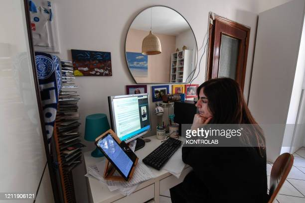 Woman works from her home in streaming contact with a colleague. The Italian government has ordered the closure of all schools and offices until...