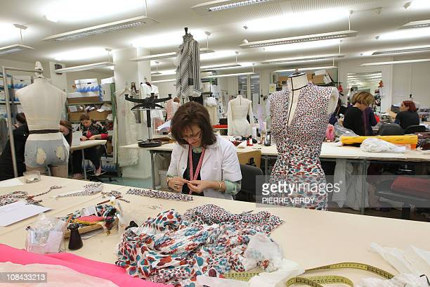 A woman works on a dress designed by French JeanPaul Gaultier on January 23 2011 in his studio in Paris ahead of Gaultier's SpringSummer 2011 Haute...