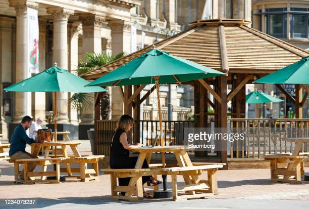 Woman works on a laptop under a parasol in Victoria Square in Birmingham, U.K., on Tuesday, July 20, 2021. The U.K.'sMetOfficehas issued its...
