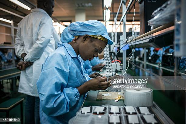 A woman works on a phone at the VMK factory in Brazzaville on July 20 2015 The factory run by Verone Mankou produces the first cell phones made in...