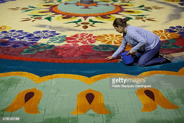 A woman works on a sawdust carpet in the early hours along the streets during the Corpus Christi feast on June 7 2015 in Elche de la Sierra near...