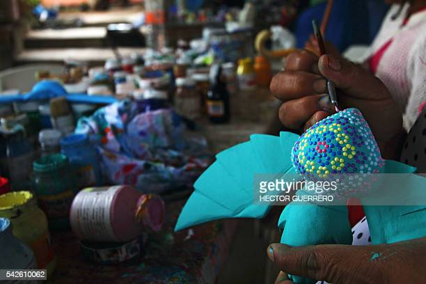 A woman works on Alebrijes in a crafts workshop in San Antonio Arrazola Oaxaca State Mexico on 22 June 2016 Alebrijes are coloured Mexican folk art...