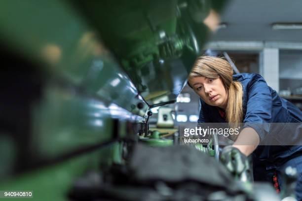 mulher trabalha em uma máquina de moedura interna. fase de metal, acabamento de peças - metalúrgico - fotografias e filmes do acervo