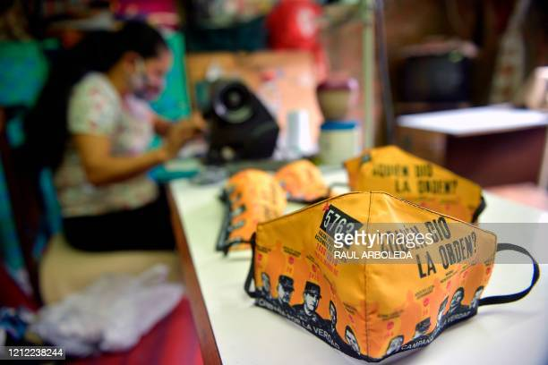 A woman works on the making of face masks reading Who gave the order for the Mothers of False Positives civil organization in Soacha Colombia on May...