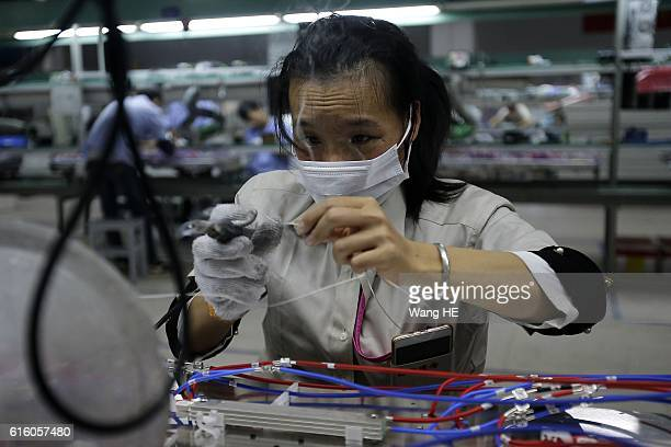 A woman works on the production line at Hongxin Communication Technology Company on October 21 2016 in Wuhan Hubei province China Hongxin...