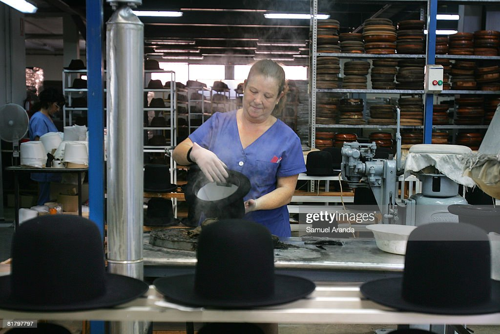 15ef16432a222 A woman works on the production of the large black hats worn by ...