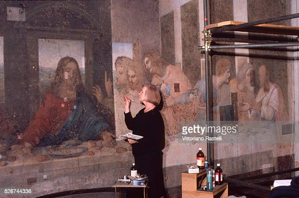 A woman works on the restoration of a fresco painting Milan Italy